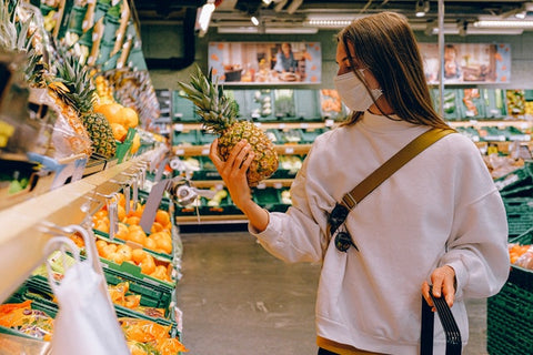 A woman buying healthy fruits in a supermarket with pineapple in her hand