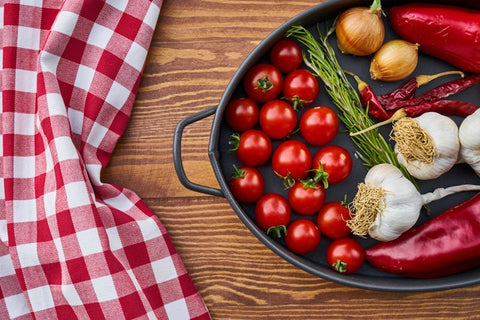 A pan containing cherry tomatoes, chilli, garlic, onion and a red table cloth