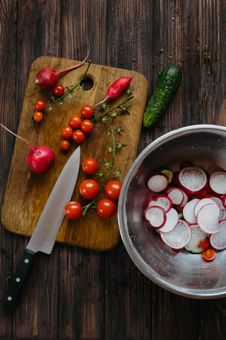 A cutting board with cherry tomatoes, cucumber, radishes and other healthy vegetables