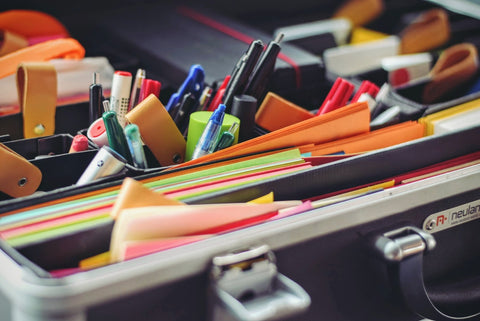a drawer with organized colorful notepads, post-its, pens, and other office stationary