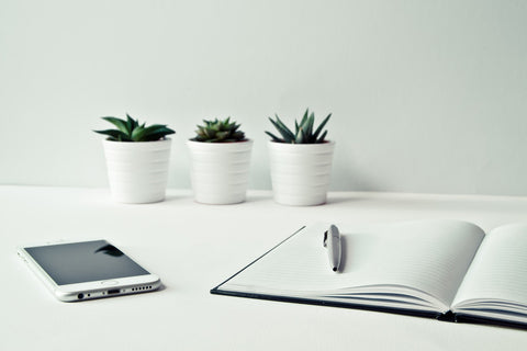 a white desk with three white pots, white phone and a white laptop to make office space productive