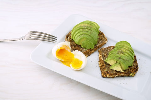 Fork and an avocado and egg breakfast dish