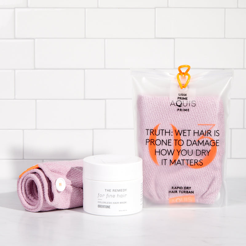 light pink towel in bag and remedy hair mask for fine hair on shower shelf