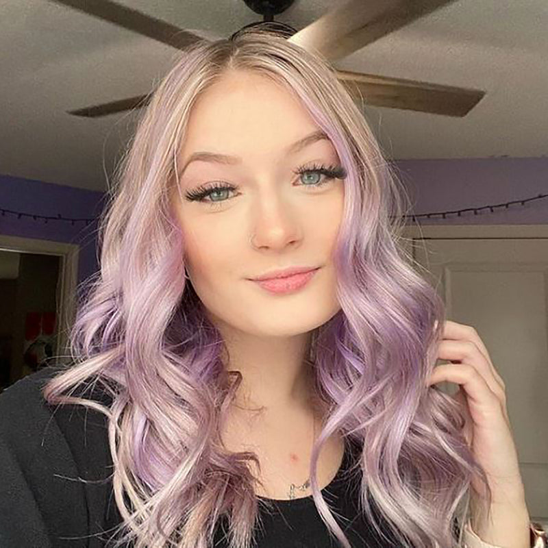 person with pastel purple hair color on shoulder length pre-lightened hair