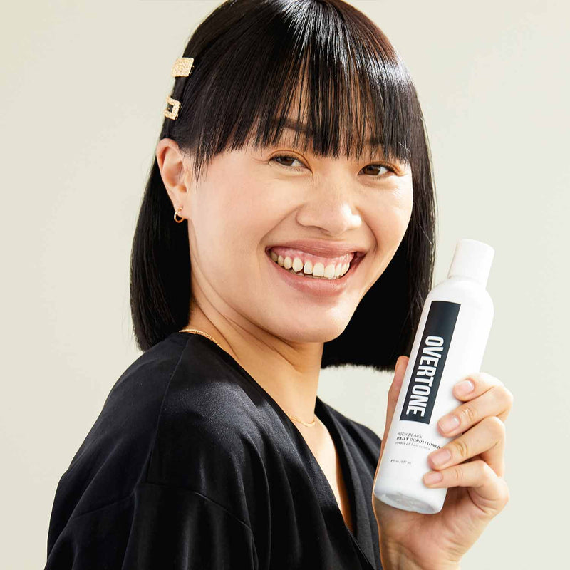 person with strait black hair color with short hair and bangs holding oVertone rich black daily conditioner