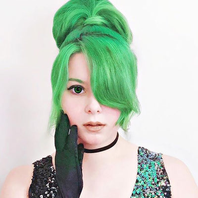 person with bright green, pre-lightened hair in a high ponytail with bangs wearing black gloves and sequin top