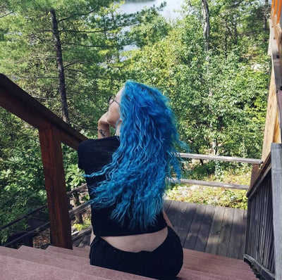 person with long turquoise hair color on pre-lightened curly hair