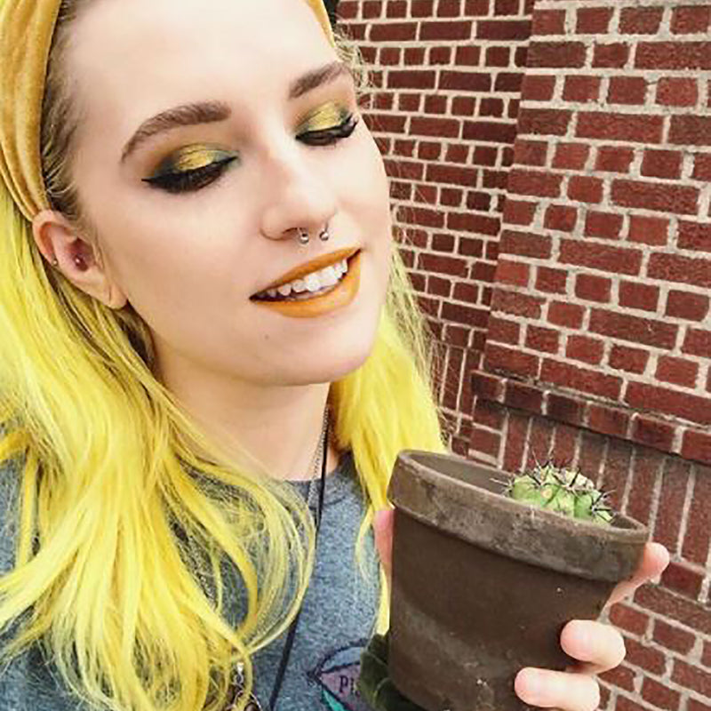 person with yellow headband and bright yellow, medium length pre-lightened hair holding a small potted cactus