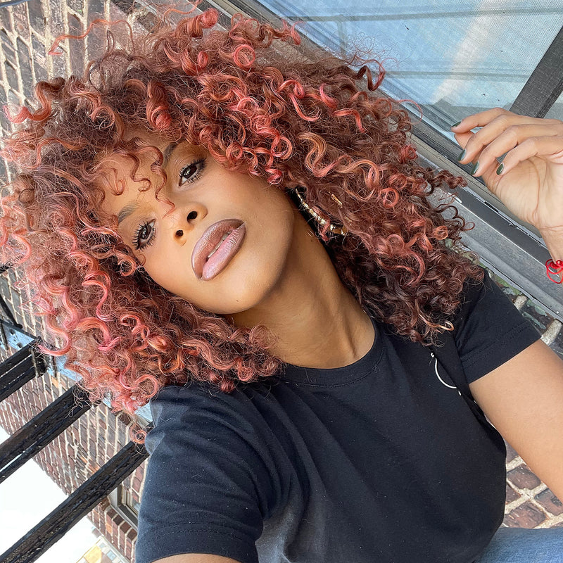 person with curly rose gold hair color on pre-lightened shoulder length hair