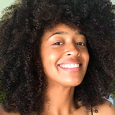 person with curly hair after wearing the remedy hair mask