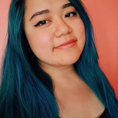person with teal hair color on shoulder length pre-lightened long hair