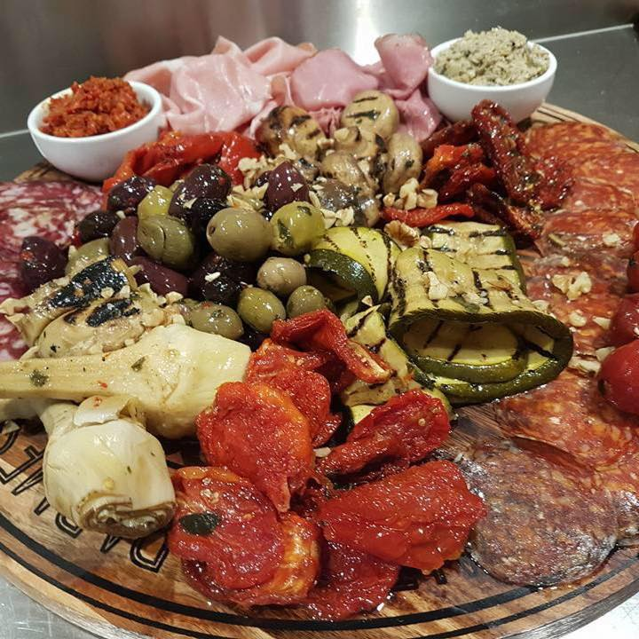 Antipasto Round wooden board with preserved vegetables, salami and dips