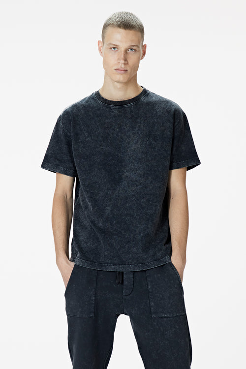 Male Model wearing the washed black tee-shirt- BODA SKINS. Front Facing.