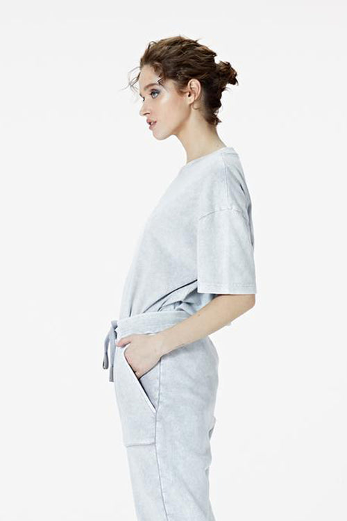 Female Model wearing the washed grey tee-shirt- BODA SKINS. side Facing.