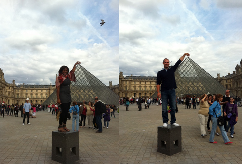 Nadia and Sebastian pretending to touch the tip of the glass triangle marking the entrance to the Louvre.