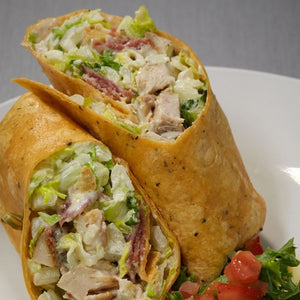 Chicken Caesar Wrap filled with chicken, bacon, tomatoes, lettuce and homemade dressing.