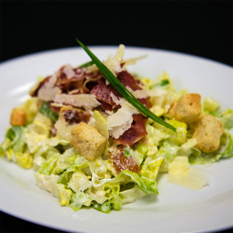 Salad made of romaine lettuce, bacon, fresh croutons and homemade caesar dressing.