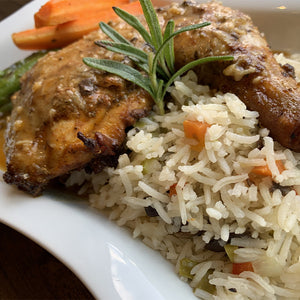 Plate with piece of oven roasted chicken, vegetable fried rice and steamed vegetables.