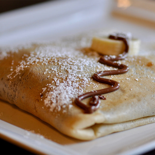 Folded crêpe with icing sugar and Nutella on top.
