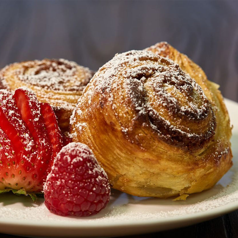 Homemade made-from-scratch puff pastry cinnamon sugar rolls with fresh fruit.