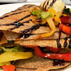 Vegan buckwheat crepe with bell peppers, brussels sprouts, onions, zucchini, hummus and balsamic glaze.