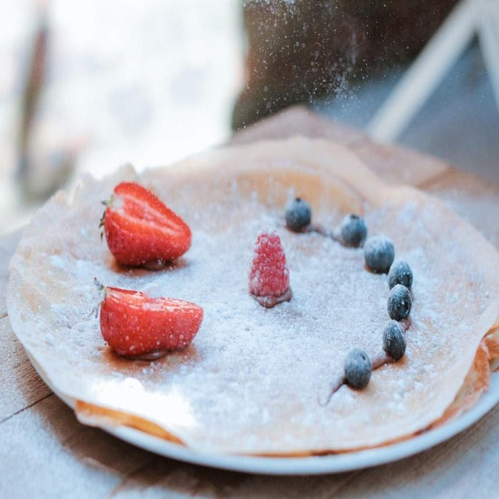 A delicious crepe you can design yourself. This is an image of an icing sugar coated crepe with fruit arranged in a smiley face.