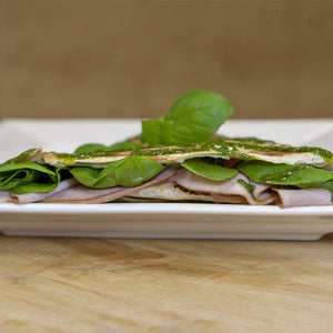 Crêpe filled with black forest ham, Swiss cheese, and greens, topped with pesto drizzle and basil leaves.