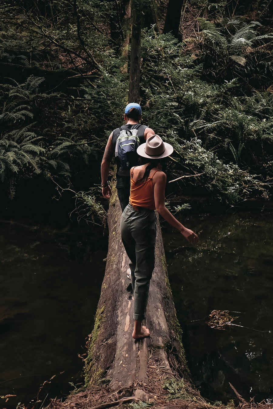 Couple walks across a log over a creek on Hike & Seek day tour from Melbourne