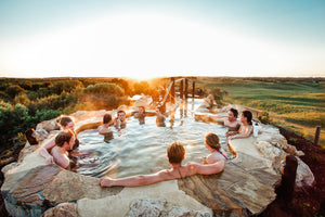 Group of friends soak on hot pools at Peninsula Hot Springs