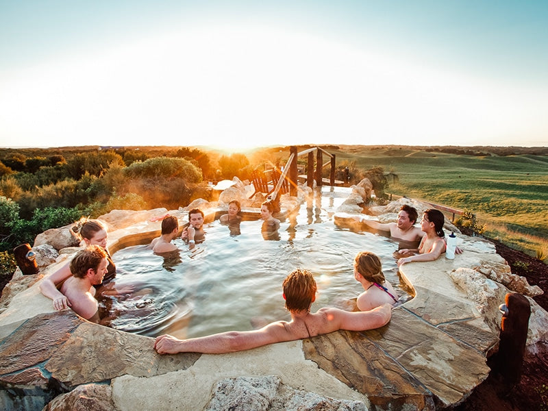 Group of friends soak on hot pools at Peninsula Hot Springs during Hike & Seek tour