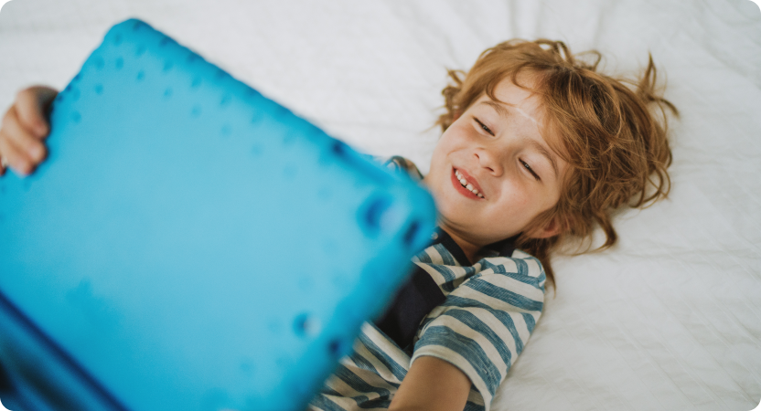 A child holding a tablet device and smiling