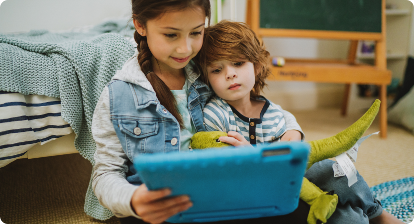 An older child reading to a younger child from a tablet device