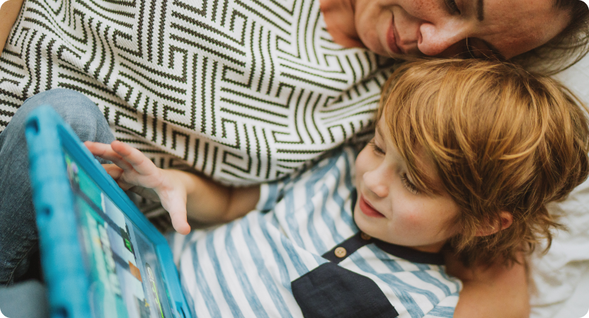 A woman embracing a child as they read from a tablet screen together