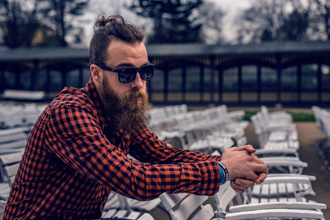 A bearded man in sunglasses leaning against the back of a chair outside.
