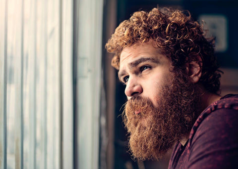A person with a thick beard staring out a window.