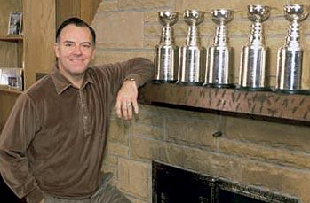 Scotty Bowman posing next to his trophies