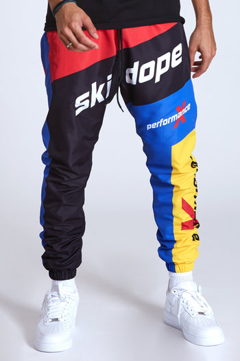 DOPE 100% Polyester windbreaker pants with elastic jogger ankle. #Red/Black