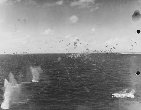 Japanese Carrier Division 3 under attack by U.S. Navy aircraft from Task Force 58, in the late afternoon of 20 June 1944. Anti-aircraft shell bursts are visible in the upper right. Photographed from a USS Bunker Hill (CV-17) aircraft.