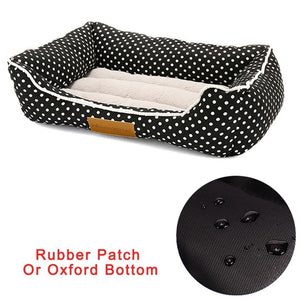 rectangular cream and black pet bed with a white polk a dot patter and rubber bottom