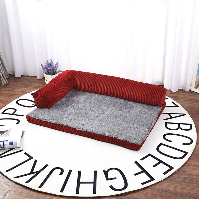 rectangular  red and grey pet bed placed on top of a round rug with the alphabet on the edge of the rug