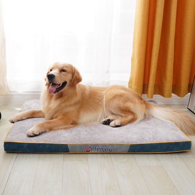 golden retriever lying on a thick black base and cream top dog mat infront of a window
