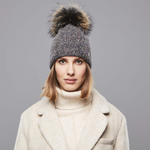 A woman wearing a Chaos New England Pom Beanie in Dark Brown