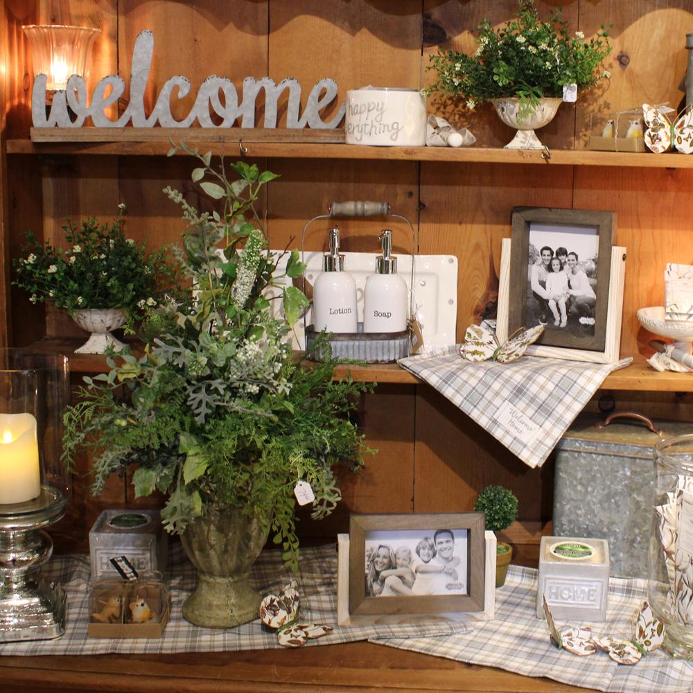 A closeup of a shelf unit with a variety of home decor items including: galvanized welcome sign, floral arrangements, soap and lotion set, picture frames, salt and pepper shakers and more.