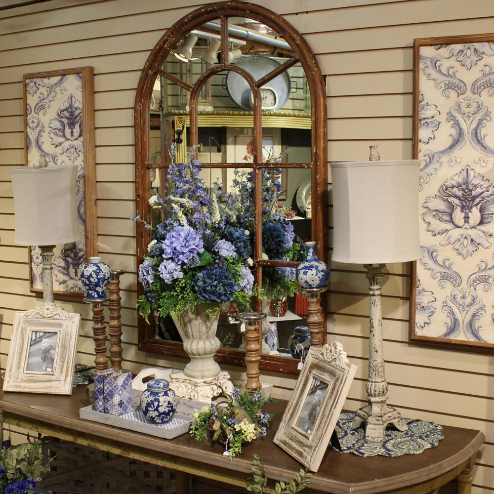 A collection of blue and white themed decor around a large mirror.  Floral arrangements, picture frames, lamps, and vases.