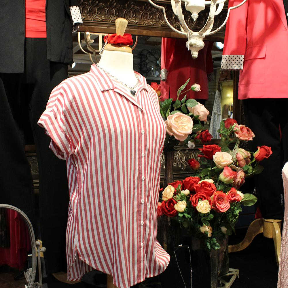 A mannequin with a red and white vertical stripe blouse next to vases of red, white and pink roses.