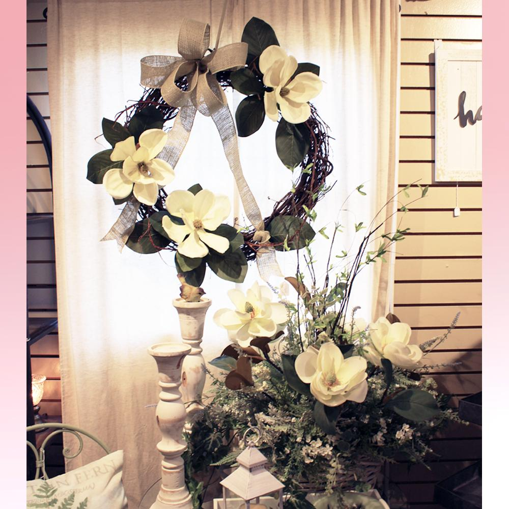 A Magnolia wreath with bow hung behind an accompanying table top arrangement.  Next to the arrangement are two tall wooden candlesticks