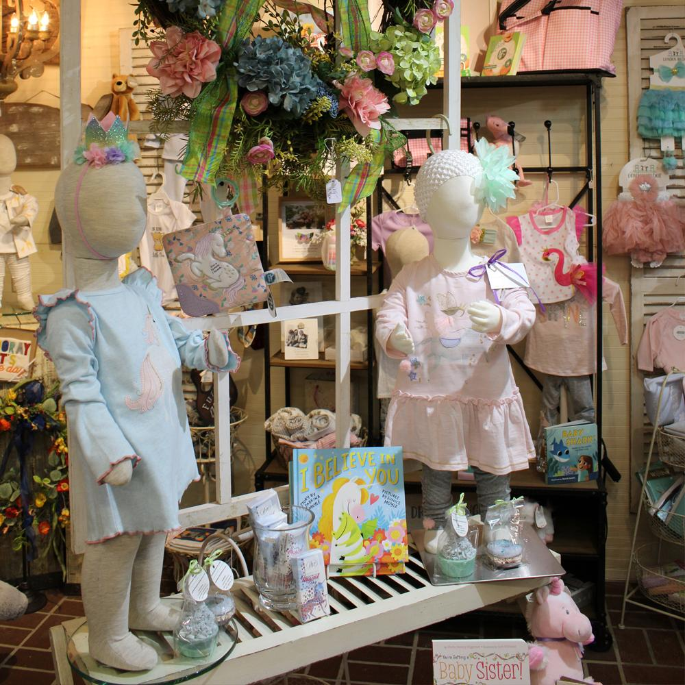 A display of kids clothing on mannequins surrounded by assorted toys, books, and accessories for boys and girls.