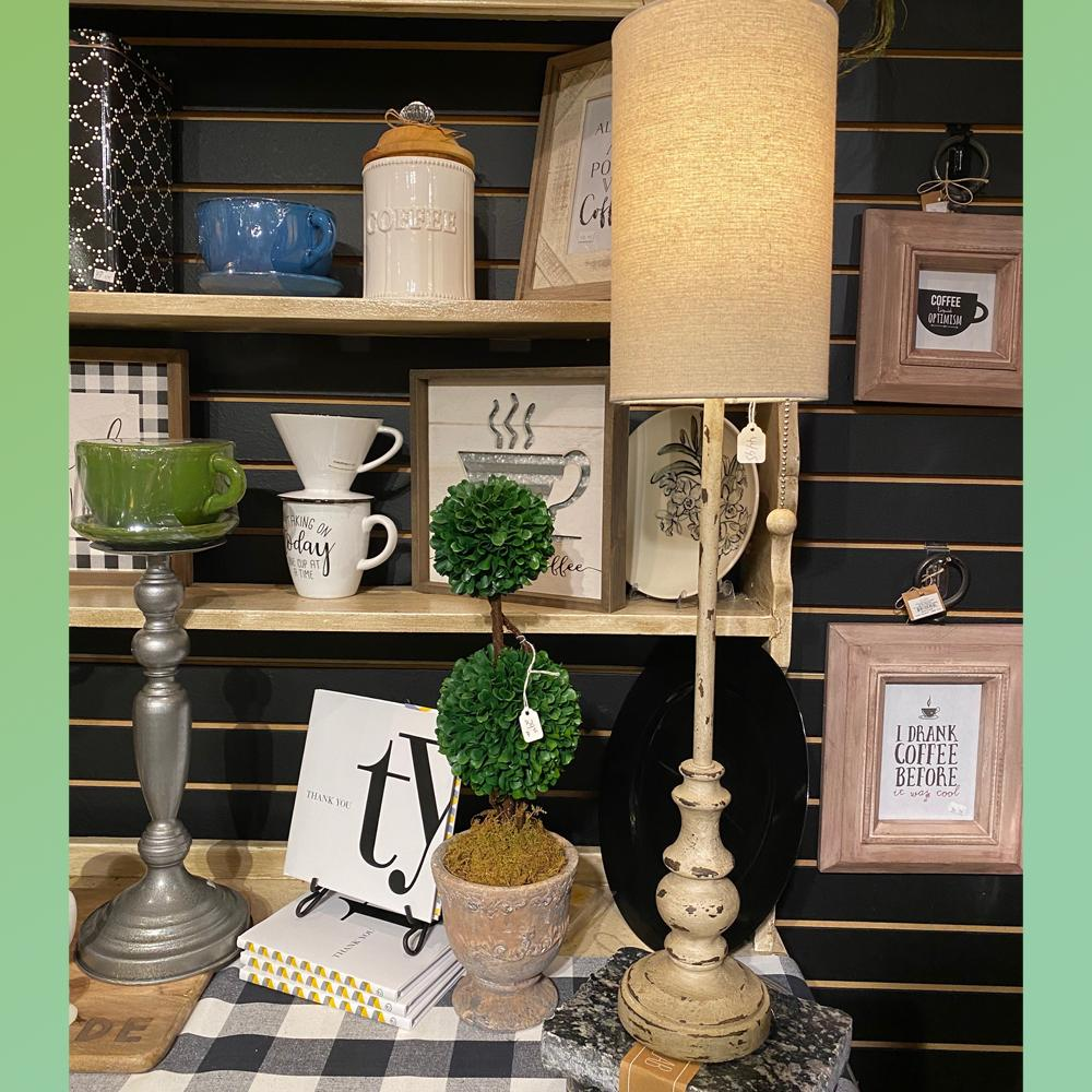 A buffet lamp in front of a shelf filled with coffee cups, art, and cookie jars.  To the left of the lamp is a table top topiary, a Thank You book, and a coffee mug candle on a candlestick