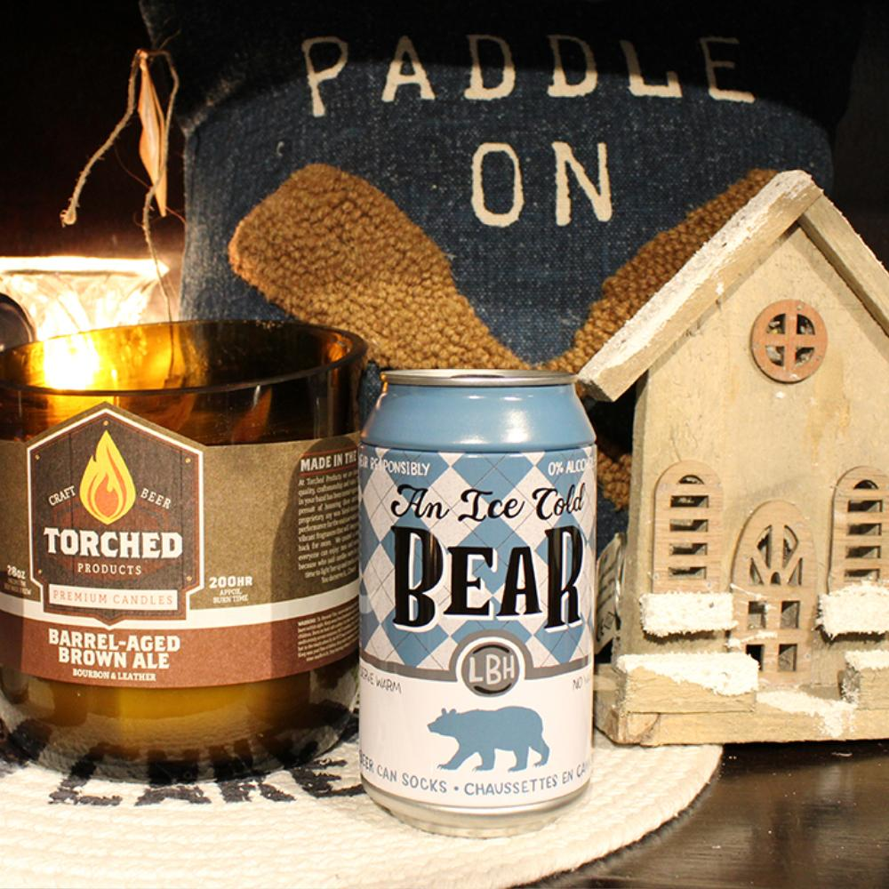 A multi wicked candle, socks in a beer can, and a decorative wooden Christmas house sit in front of a pillow that says 'Paddle On'