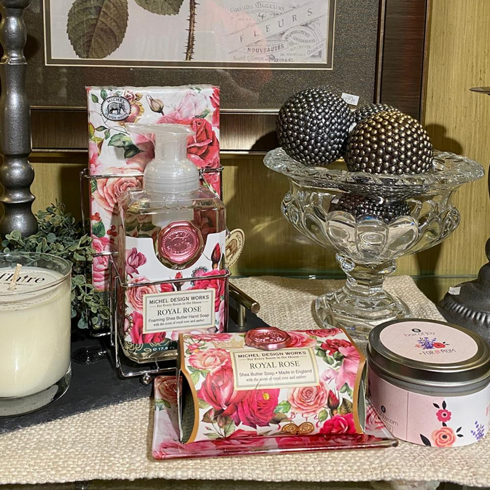 A collection of hand soap, and bar soap wrapped in illustrated red and pink roses, nestled between a candle in a clear vessel and a candle in a closed tin.